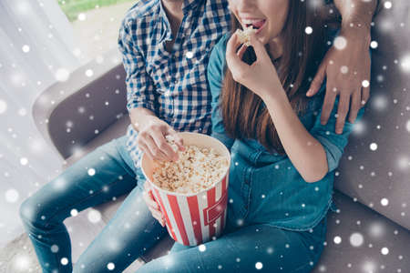 Cropped close up top view photo of young beautiful couple, which is at home, eating popcorn from a box and watching comedy at nice atmosphere, snowflakes on background