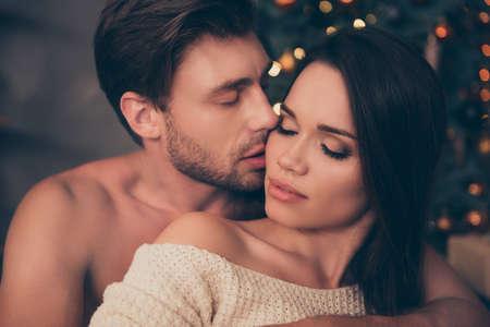 Primer plano de la pareja morena con cerdas sostienen a su morena desde atrás, sentimientos lindos, placer de tentación, piel suave, intensa, tierna, celebran la Navidad