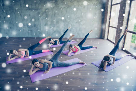 Five concentrated cute fit young ladies, stretching and holding their legs by doing exercise, wearing fashionable sport wear, barefoot on a purple carpets in loft modern studio, snowflakes background