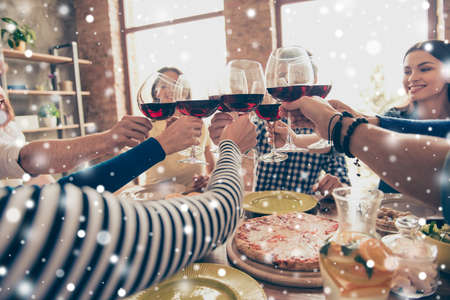 Close up photo of glasses with wine. Young people are toasting to celebrate victory together, Table is full of tasty food and drinks, snowflakes background, winter holiday Stock Photo