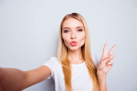 Beautiful young pretty woman with straight blonde hair sending air kiss and showing victory sign to her boyfriend via video connection. She is isolated on grey background