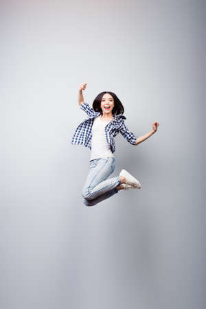 Concept of freedom, happiness and life without problems. Vertical full length portrait of happy crazy woman is jumping up, isolated on grey background Stock Photo