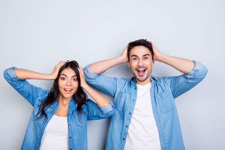 Really? Portrait of two young shocked lovers are amazed with wide open eyes and mouth holding heads in casual wear standing over grey background