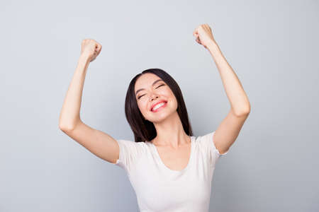 Close up of overjoyed, successful young manager closed her eyes  with two hands raised and celebrating victory while standing in front of grey background