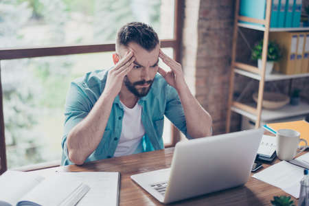 Sluit omhoog portret van ernstige geconcentreerde kerel in slim toevallig denimoverhemd, zittend bij de Desktop in bureau en het werk met laptop. Hij is geconcentreerd met ideeën Stockfoto