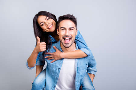 excited two people in love is having fun, they adore each other. Pretty joyful lovely smiling woman is sitting on her boyfriend's back and showing thumb up, they are isolated on grey background Foto de archivo