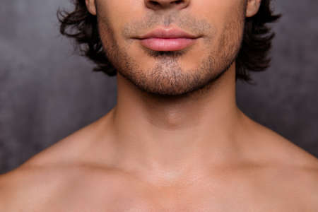 Bliska przycięte zdjęcie szczeciny gorącego faceta, brody, ma doskonałą skórę i włosy, na białym tle na szarym tle. Fryzjer, strzyżenie brody, golenie i koncepcja stylizacji Zdjęcie Seryjne