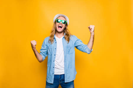 Yes! Lucky young hipster man isolated over yellow background, happy man wearing glasses and hat acts like he won something with raised hands, emotion, success, gesture and people concept Banco de Imagens