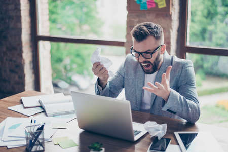 Frustrated bearded brunet entrepreneur, yelling at his laptop in office and cramps the documents, going crazy and insane, in black specs and formal wear, grey jacket Stock Photo