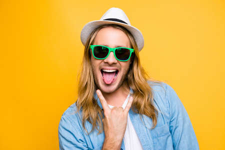 Rock n roll babe! Closeup portrait of cool young playful hipster man in casual outfit showing his tongue and rock on gesture, standing over yellow background Banco de Imagens