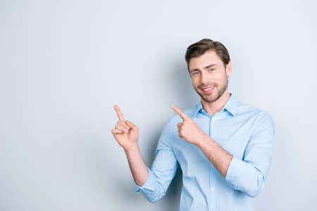 Advertisement concept. Successful caucasion man with beaming smile on grey background  is pointing on empty copy space with his fingers Stock Photo