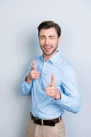 Isolé, confiant, sourire, à, blanc, dents, homme, pointage, vers, sien, index, et, clin d'oeil, à, appareil-photo, sur, arrière-plan gris Banque d'images - 89873178