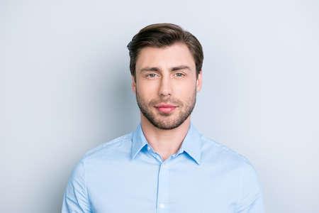 灰色の背景の上の種類と立っている間は少しトリッキーな視線カメラを見て成功した黒髪の男の肖像画間近します。