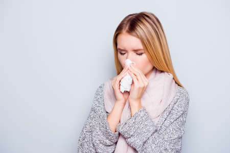 Closeup portrait of beautiful charming attractive woman sneezing in a tissue blowing her runny nose, having a cold standing over grey background Stock Photo