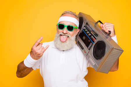 Netter aufgeregter gealterter kühler Pensionärgroßvater des lustigen aktiven sexy Athleten im Eyewear mit Bassausschnittghettoblasterrekorder. Alte Schule, Beute, Zunge kleben, Narren, Fitnessstudio, Training, Technologie Standard-Bild - 89873192