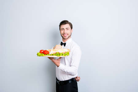 We have royal service in our restaurant, we are always ready to make you feel on cloud nine. Waiter is holding a large tray with an appetizer, isolated on grey background Stok Fotoğraf