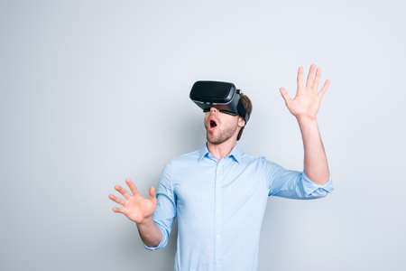Close up of cheerful student in shirt wearing virtual reality goggles, getting experience using VR-headset of virtual reality, gesticulating, touching something with his  hands  while standing over grey background