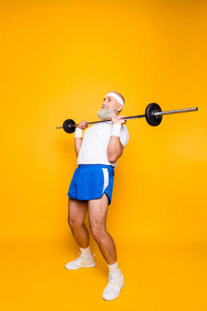 Full length of confident cool grandpa with serious grimace exercising holding equipment, lifts it up, wears sexy shorts, sneakers. Body care, hobby, weight loss, deadlift, powerlifting, pressure 版權商用圖片 - 89873078