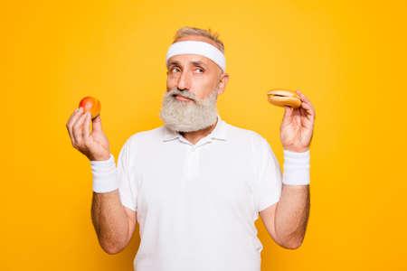 El abuelo fresco del atleta sostiene la hamburguesa y la fruta prohibidas del junkfood. Pérdida de peso, decisión, motivación, cuidado de la salud, fuerza, prohibición, entrenamiento, gimnasio, régimen, cuidado corporal, calorías, estilo de vida