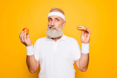Athlete cool grandpa holds forbidden junkfood cheeseburger and fruit. Weightloss, decision, motivation, healthcare, strength, prohibition, workout, gym, regime, bodycare, calories lifestyle Archivio Fotografico