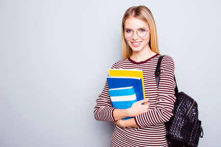 Smiling and confident young lady with a book in hands and a backpack on her shoulder is going to apply for university