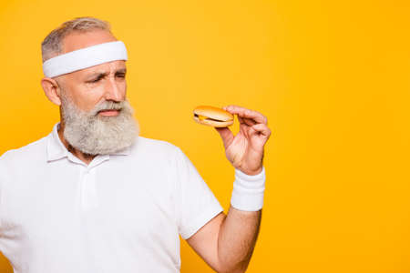 Mature modern athlete cool grey haired pensioner grandpa holds yummy tasty delicious heavy grossy sandwich. Weightloss, pride, motivation, healthcare, gym, strength, power, bodycare lifestyle