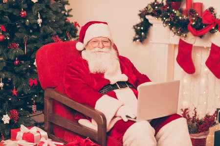 Holly jolly x mas, noel voorbereidingen! Close-up van vriendelijke positieve santa, studie lijst met kinderwensen en geschenken op apparaat, klaar om dromen waar te maken, breng geluk aan kinderen Stockfoto - 89872852