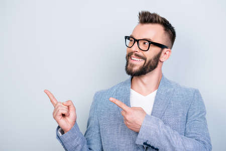 Close up portrait of young successful brunete bearded stock market broker guy on the pure light background, he is smiling, wearing suit and is pointing on a copyspace with his fingers Stock Photo