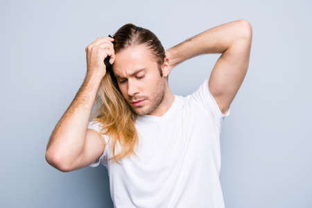 Handsome concentrated young man in casual clothes is combing his long blonde hair and making a ponytail, isolated on grey background