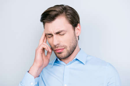 Close up portrait of confident entrepreneur having a headache, he has eyes closed and he is touching his temple while standing over grey background. Stress and health care concept