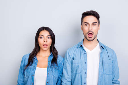 It's unbelievable! Portrait of two shocked and surprised people dressed in denim clothing. They are standing with open mouths because they won a prize, isolated on grey background