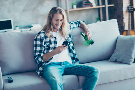 Happy and relaxed man has weekend after hard work. He is drinking beer and reading the latest news on the Internet using his smartphone.