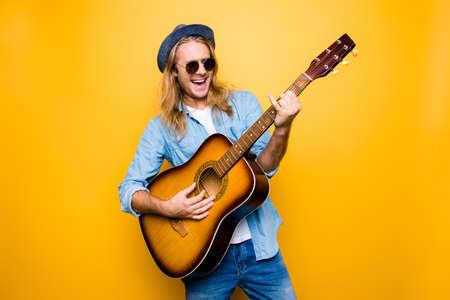 音楽は私のライフ スタイル!カジュアルな服装と眼鏡のアコースティック ギターを演奏し、歌を歌いながら服を着て興奮している、のんきなミュー