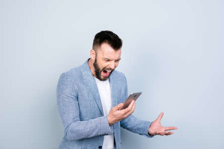 Going crazy and insane, psycho and agression. Close up portrait of shouting stressed young brunet bearded entrepreneur, yell at his phone, on pure light background, wearing casual smart