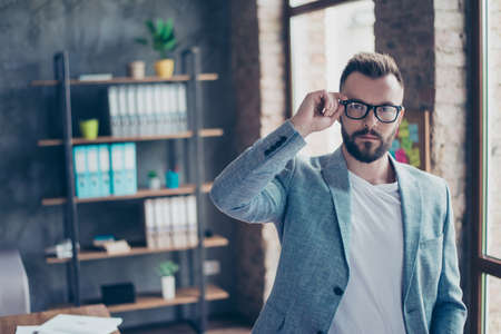 Serious stylish ponder brunet bearded broker with mustache, looking at the camera, standing in a casual smart near the window in office, so hot, ponder, pensive, virile macho