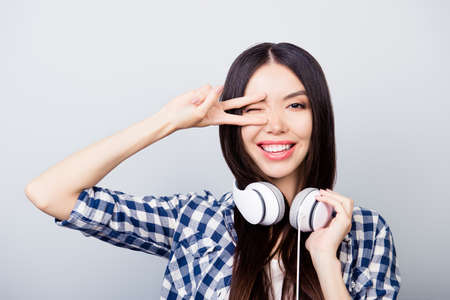 Beautiful relaxed asian girl with dark long hair, toothy smile is giving a wink, showing v-sign and listening to her favourite song, isolated on grey background 版權商用圖片