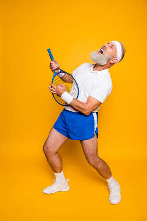 Full length of sexy emotional cool pensioner grandpa practising rock music on a  sport equipment, stands in pose, yell and shout. Body care, hobby, weight loss, lifestyle, strength and power, health Imagens