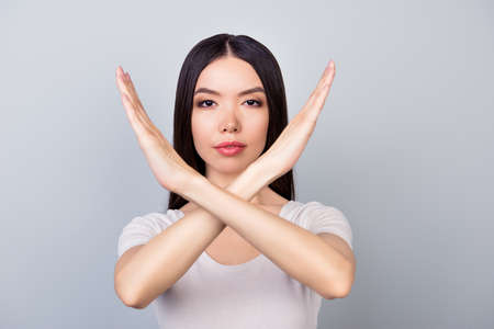 Close up of young brunette woman making stop gesture, forbidding something, standing in white outfit  on a grey background Stock Photo - 89872542