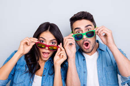 Concept of large sales and discount. Close up photo of two excited and wondered people with open mouths dressed in casual clothes, they are touching colorful glasses, isolated on grey background Banco de Imagens