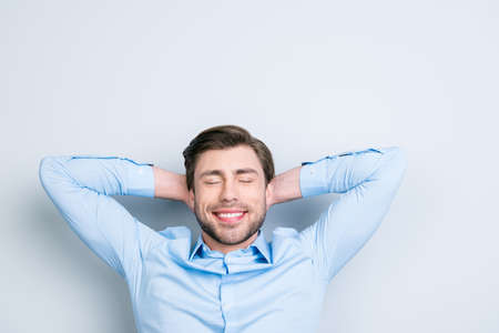 Time to relax.Close-up portrait of cute young dreaming man with closed eyes holding hands behind his head having time-out while standing over grey background Stock Photo