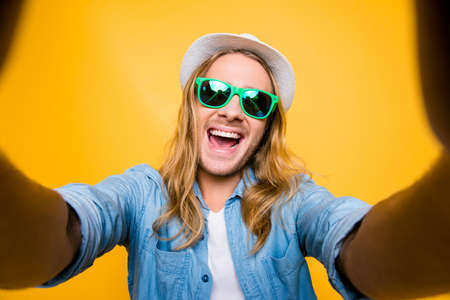 Selfie mania. Just me and no one else. Top view of funny hipster man in hat and summer glasses taking selfie and smiling standing over yellow background