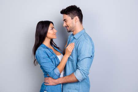 人と女性間のロマンチックな関係の概念。ムラート ブロンズ肌女性とハンサムな男顔に立っているし、灰色の背景上に分離されて、お互いにキスし 写真素材