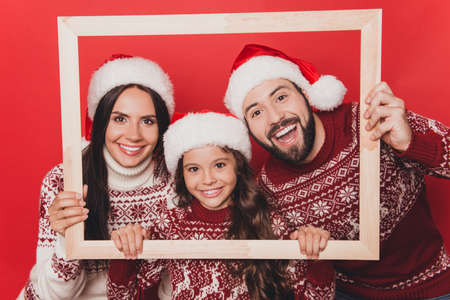 Adorable sweet caucasian couple with small cute girl bonding, so excited in knitted cute traditional x mas costumes with ornament, head wear, december, noel time, hold frame Stock Photo