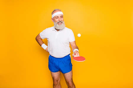 Competetive emotional cool active comic grandpa with beaming grin, with table tennis equipment. Healthcare, weight loss, bodycare lifestyle, wearing blue sexy shorts, so hot! Banco de Imagens