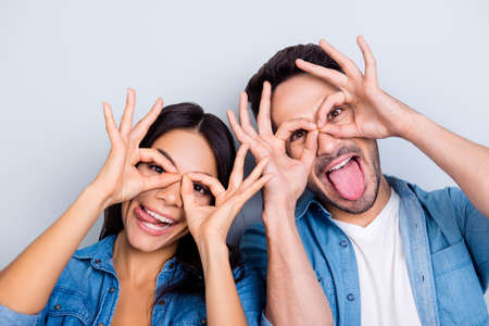Concept of having funtime and grimacing, behaving like kids. Close up photo of two happy people making binoculars with their hands and showing tongues. Isolated on grey background