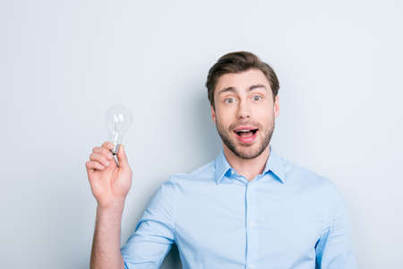 Close up portrait of emotional smart cheerful student with bristle holding a lightbulb and has founded a great new solution while standing over grey background