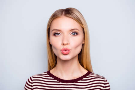 astonishing: Close up portrait of amazing woman pulled her lips to kiss someone, blowing kiss to camera, sending kiss with full lips, gives a kiss,   standing over grey background Stock Photo