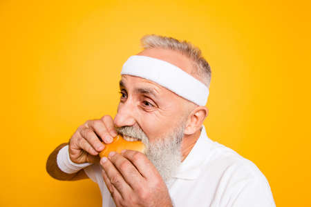 Weightloss, healthcare, gym, strength, regime, challenge. Close up of modern athlete cool grey haired pensioner grandpa hold yummy tasty delicious heavy grossy sandwich, destroys it