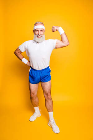 Full length of cheerful excited mature goofy cool pensioner grandpa champion practising bodybuilding, showing off his pumped hand. Body care, strength, leadership, motivation lifestyle Stock Photo