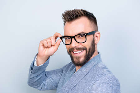 Close up of successful young handsome brunet bearded businessman in formal outfit and black glasses on pure background. So cheerful and stylish, attractive and smart Stock Photo